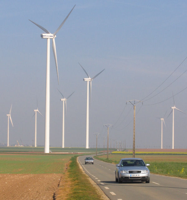 Wind turbines beside road in France and cars